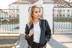 Charming young woman the blonde in a black spring stylish jacket in black jeans in a white shirt poses near vintage gate. Against a white building. American royalty free stock photos