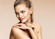 Charming young woman with blonde hair. Photo of beautiful woman with healthy skin on beige background. Youth and skin care concept Royalty Free Stock Photography