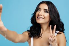 Charming young woman with bright smile dressed in white swimsuit taking selfie on the blue background stock images