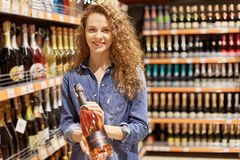 Charming young woman with brown curly hair , in denim clothes. Holds bottle of alcoholic drink, stands near supermarket shelves ,. Finds wine or champagne royalty free stock photography