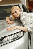 Charming young woman buying new automobile stock photo