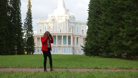 Charming young woman calls her boyriend by mobile in an autumn park. Beautiful girl stands in a picturesque autumn park, dressed in red coat, black leggings, and stock video footage