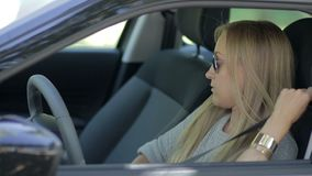 Charming young woman in car fastening seat belt stock video