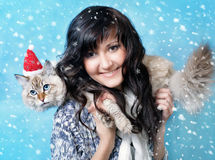 Charming young woman with cat in santa cap Stock Images