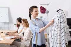 Charming young woman checking cardigan lapels. Nicely done. Pretty young women holding lapels of a cardigan hanging on a mannequin while her colleagues Royalty Free Stock Photos