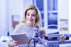 Charming young woman checking details in internet. So pleased. Pleased blonde expressing positivity and looking at her gadget Royalty Free Stock Images