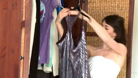 Charming young woman choosing clothes. In her bedroom stock video