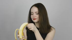 Charming young woman eating a banana and smiling. Concept of eating fresh fruits vegetarian stock video footage