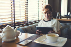 Charming young woman have video conversation while breakfast in coffee shop Stock Photography