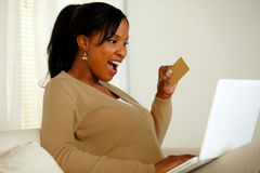 Charming young woman holding a gold credit card Royalty Free Stock Photos