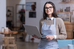 Charming young woman holding laptop and smiling. Ready to work. Beautiful ambitious woman smiling and holding laptop while standing in a cafe Royalty Free Stock Photo