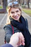 Charming woman in the park. Charming young woman holding a man`s hand smiling at the camera in the park Royalty Free Stock Image