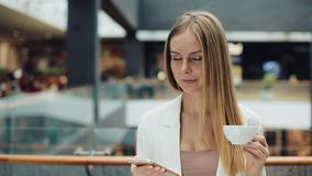Charming young woman holds smartphone in one hand and cup of coffee in another sitting in the cafe stock video footage
