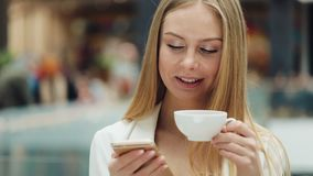 Charming young woman holds smartphone in one hand and cup of coffee in another sitting in the cafe stock video