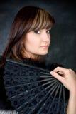 Charming young woman with italian fan. Fashion studio portrait Stock Photos