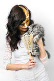 Charming young woman with kitten. Charming young woman in venetian mask with scotch kitten Royalty Free Stock Images