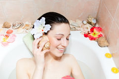 Charming young woman listening to seashell in bath Stock Images