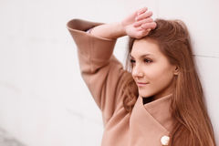 Charming young woman with long brown hair in a beige coat Royalty Free Stock Image
