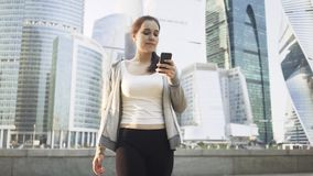 Smiling young woman looking at her smartphone in a Moscow city street. Charming young woman looking at her smartphone in a Moscow city street on a sunny summer stock video