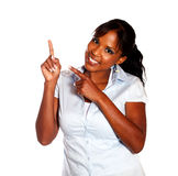 Charming young woman looking at you pointing up Stock Photos