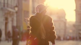 Young woman with long hair, big blue eyes in a gray is rushing in the city-center, than turns to camera and smiles. Charming young woman with a magnificent long stock video