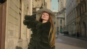 Young woman with long hair, big blue eyes in a gray is rushing in the city-center, than turns to camera and smiles. Charming young woman with a magnificent long stock video footage