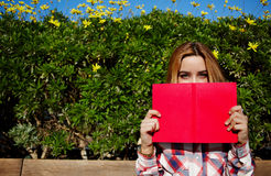 Charming young woman with pink book held up close to her face Royalty Free Stock Image