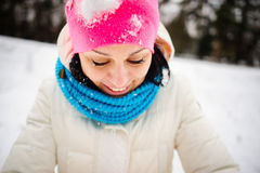 Charming young woman plays with someone in snowballs. The first snow and winter entertainments very much please. The bright hat is closed up with snow. The royalty free stock image