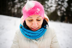 Charming young woman plays with someone in snowballs. The first snow and winter entertainments very much please. The bright hat is closed up with snow. The Stock Photo