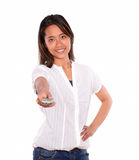 Charming young woman pointing with remote control Stock Photos