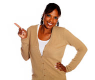 Charming young woman pointing right looking at you Royalty Free Stock Image