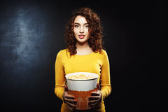 Charming young woman with popcorn bucket isolated on black background. Charming young woman in yellow sweater with popcorn bucket on black background looking Royalty Free Stock Photo