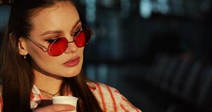 Charming young woman in red sunglasses drinks coffee in the rays of evening sun stock video