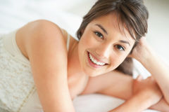 Charming young woman relaxing on bed Stock Photo
