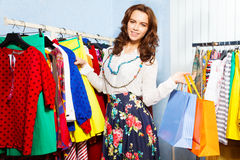 Charming young woman with shopping bags in mall. Charming young woman holding chosen clothes with shopping bags in mall Stock Photo