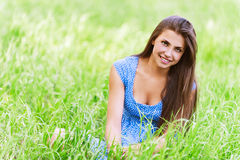 Charming young woman sitting green Royalty Free Stock Image