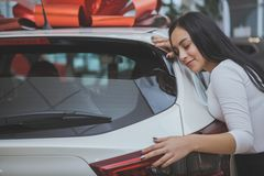 Lovely young woman buying new car at the dealership stock photography