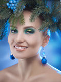 Charming young woman smiling in studio with xmas tree-wreath on Royalty Free Stock Photo