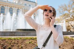 Charming young woman in sunglasses talking on mobile phone outdoors Stock Images
