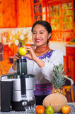 Charming young woman in traditional andean dress standing inside kitchen holding lemon over juice maker, healthy Royalty Free Stock Photos