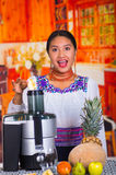 Charming young woman in traditional andean dress standing inside kitchen inserting apple pieces into juice maker Stock Photo