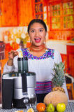 Charming young woman in traditional andean dress standing inside kitchen inserting apple pieces into juice maker Royalty Free Stock Photography