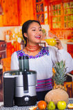 Charming young woman in traditional andean dress standing inside kitchen posing in front of juice maker drinking from Stock Images