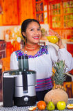 Charming young woman in traditional andean dress standing inside kitchen posing in front of juice maker drinking from Stock Photography