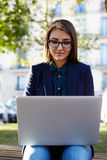 Charming young woman using laptop gadget sitting outdoors at sunny beautiful day Royalty Free Stock Photo