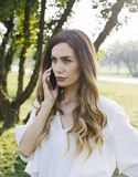 Charming young woman using mobile phone in the green park royalty free stock photos