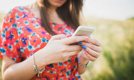 Charming young woman using to mobile smart phone. Against green of summer Royalty Free Stock Images