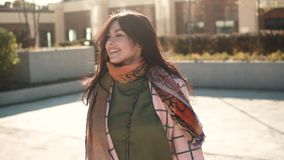 Charming young woman walks through the autumn city in a coat and smiles. cute girl on a background of modern stock video footage