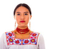 Charming young woman wearing traditional andean blouse with colorful embroideries, matching red necklace and earrings. Serious facial expression, white studio Stock Photos