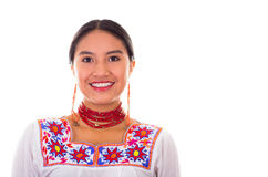 Charming young woman wearing traditional andean blouse with colorful embroideries, matching red necklace and earrings Royalty Free Stock Photo